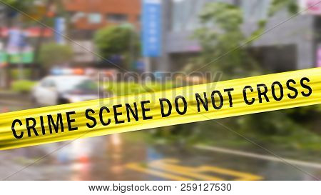 Boundary Tape And Defocused Squad Car At Crime Scene