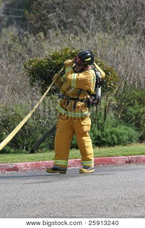 LAGUNA BEACH, CA - FEB 19: A firefighter recruit carries a firehose during fire fighting drills at the local Fire Department training area on February 19, 2009 in Laguna Beach, California.