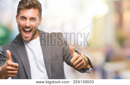Young handsome business man over isolated background approving doing positive gesture with hand, thumbs up smiling and happy for success. Looking at the camera, winner gesture.