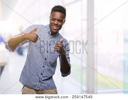 Young african american man wearing blue shirt success sign doing positive gesture with hand, thumbs up smiling and happy. Looking at the camera with cheerful expression, winner gesture.