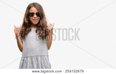 Brunette hispanic girl wearing sunglasses success sign doing positive gesture with hand, thumbs up smiling and happy. Looking at the camera with cheerful expression, winner gesture.