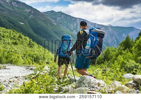 Tourists In Mountain Trek. Two Friends In Mountains. Hiking On Hills And Mounts. Hikers Walks On Roc