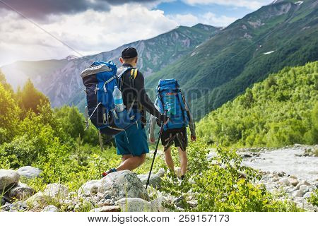 Trekking In Mountains. Mountain Hiking. Tourists With Backpacks Hike On Rocky Way Near River. Wild N