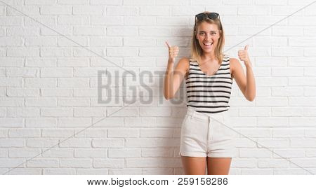 Young beautiful blonde woman over white brick wall success sign doing positive gesture with hand, thumbs up smiling and happy. Looking at the camera with cheerful expression, winner gesture.