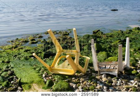 Two broken plastic chairs at the beach and sea pollution poster