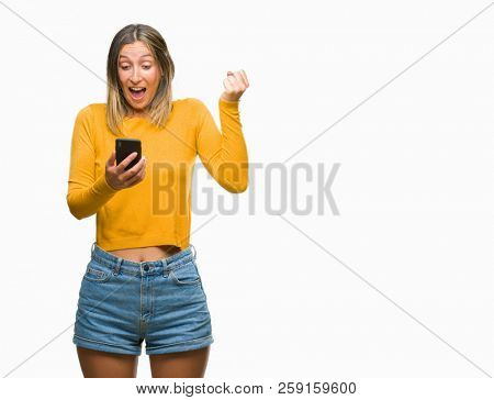 Young beautiful woman sending message using smartphone over isolated background screaming proud and celebrating victory and success very excited, cheering emotion