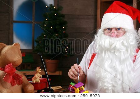 Santa Claus holds his red suspenders as he takes a break from making Christmas Presents for children around the world