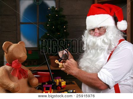 Santa Claus paints a toy as he makes Christmas Presents for children around the world