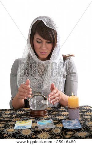 an attractive young fortune teller, looks into the future with her crystal ball, isolated on white,  with room for your text