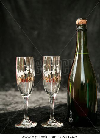 2010 champagne glasses and  bottle with its cork, on black velvet