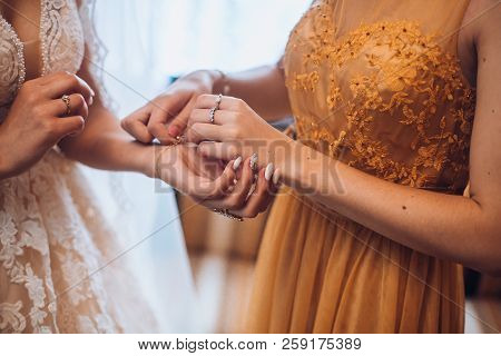Bridesmaid Preparing Bride For The Wedding Day, Helping Fasten Her Dress And Fasten The Bracelet. Br