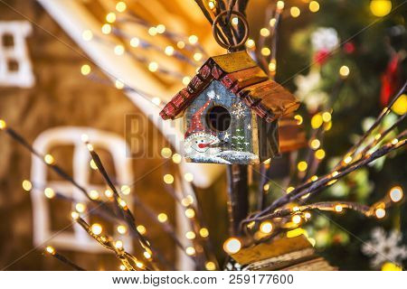 Little Bird Houses Painted With Snowmen On A Thin Tree Decorated Christmas Yellow Lights. In The Bac