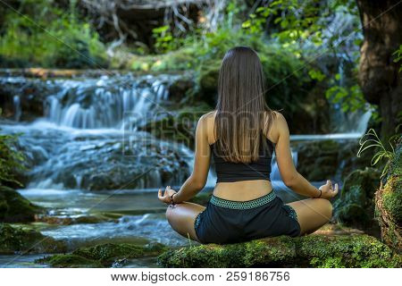 Back View Of Unrecognizable Woman Sitting In Lotus Asana And Meditating On Mossy Rock At River With