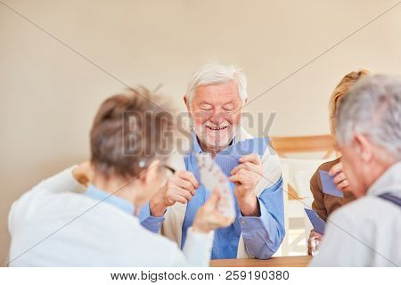 Group of seniors has fun playing cards at home or in a retirement home