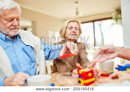 Seniors with dementia or Alzheimer's in a retirement home stack colorful building blocks together