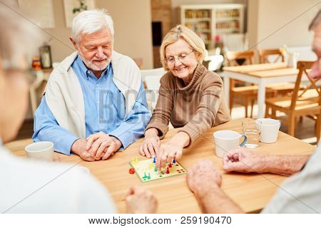 Senior couple playing a board game together in retirement home or retirement home