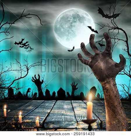 Spooky Halloween background with old trees silhouettes and zombie hand.