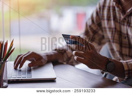 Man Using Mobile Phone And Laptop For Shopping Online By Credit Card. Pays For Purchase.online Shopp