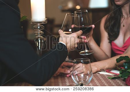 Couple In Love Holding Hands And Drinking Wine During A Romantic Dinner In A Restaurant (reduced Ton