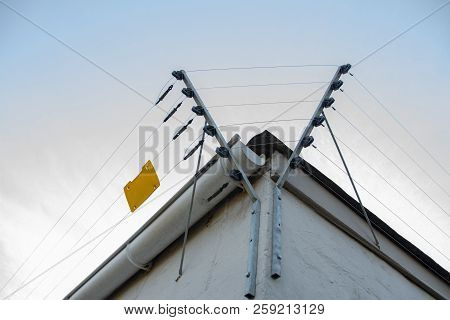 A Close Up View Of Electric Fencing Around The Top Side Of A White Building