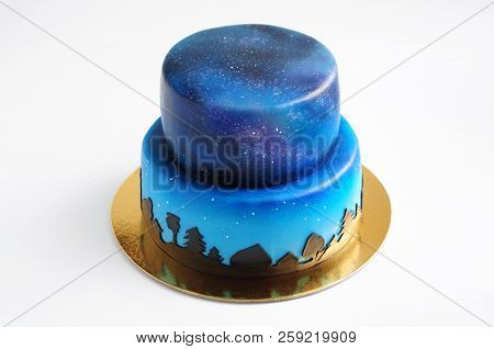 Artistic two-tiered cake with the image of the cosmos drawn by airbrush. Galaxy, stars in the night sky and silhouettes of trees. Cutout. Picture for a menu or a confectionery catalog. poster
