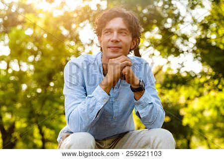 Smiling young casual man resting while sitting at the city park