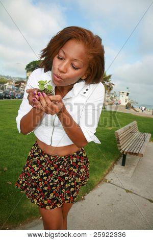 una hermosa joven tiene una planta verde para representar conceptos amable tierra