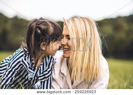 Young Beautiful Woman Cuddling With Her Little Daughter In The Park. Loving Mother And Daughter Lyin