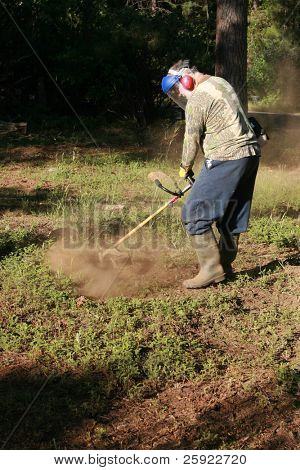 a man wears his protective gear as he cuts brush with his weed wacker