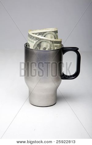 an silver aluminum travel coffee cup with two $100.00 bills inside