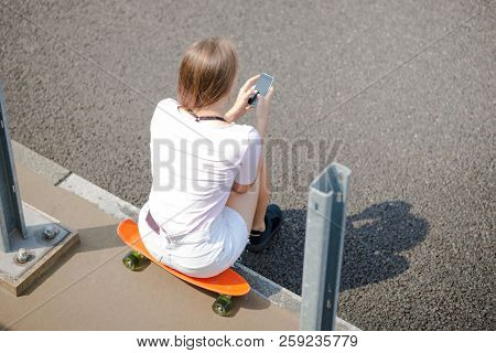 Young Beautiful Blonde Girl Using Smartphone while Sitting on the Skateboard on the Bridge