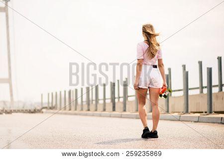 Young Beautiful Blonde Girl with Orange Skateboard on the Bridge