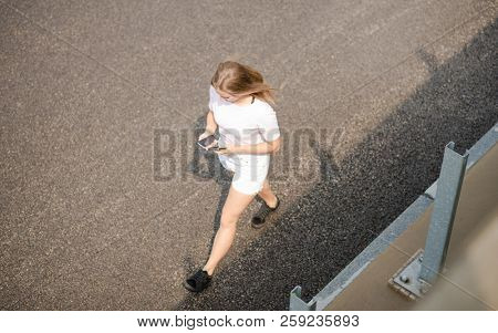 Young Beautiful Blonde Girl Using Smartphone while Walking on the Road. Top View