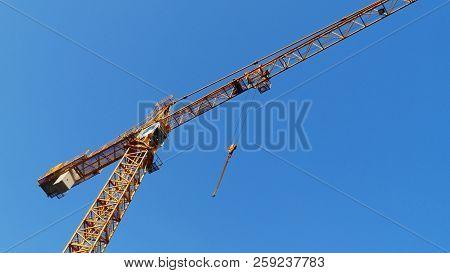Huge Crane Against Blue Sky. Industrial Crane. Hoisting Crane. Construction Site.