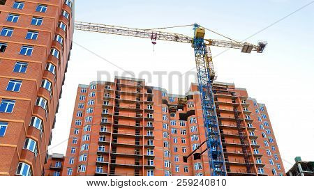 Construction Of A Multi-storey Red Brick Building. High-rise Construction. Crane Near Building Under