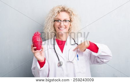 Young blonde cardiologist doctor woman over grunge grey wall holding red heart with surprise face pointing finger to himself