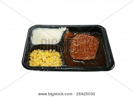 a classic salisbury steak tv dinner with mashed potatoes and corn in its black plastic tray, isolated on white