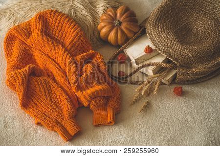 Cozy Knitted Warm Orange Sweater With Old Books And Vintage Straw Bag On White Warm Plaid With Pumpk