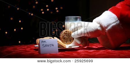 Santa Claus takes a cookie left out for him on Christmas Eve as a thank you gift for leaving presents to a grateful boy or girl