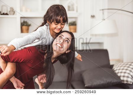 Mother And Daughter Doing Piggyback In Funny Gesture Emotion At Home. Young Sister Playing With Girl