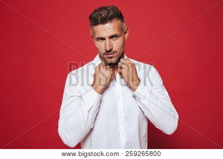 Fancy brunette man 30s with stubble in white shirt looking on camera isolated over red background poster