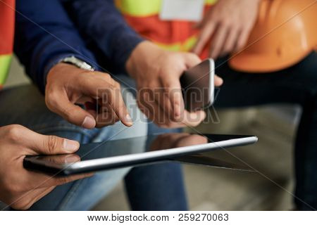 Crop Hands Of Engineers Pointing At Tablet Screen While Browsing It During Break
