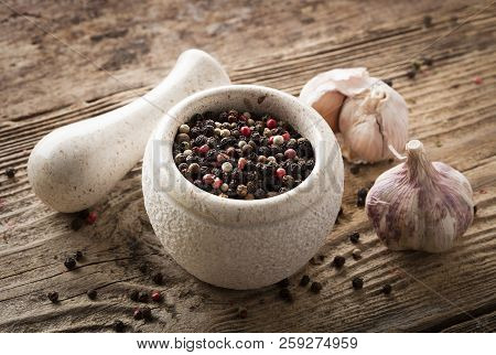 Mixed Peppercorns In Stone Bowl On Wooden Background