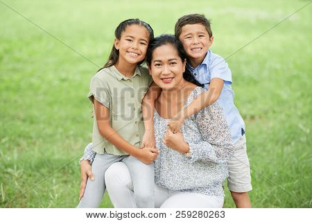 Lovely Asian Woman And Two Adorable Children Smiling And Looking At Camera While Spending Time In Pa