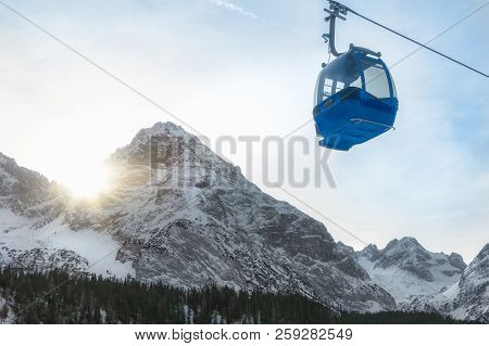 Single Cable Car Traveling In The Alps Mountains Covered By Snow, While The December Sun Shines On T