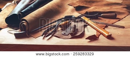 Shoemaker's Work Desk. Tools And Leather At Cobbler Workplace. Set Of Leather Craft Tools On Wooden