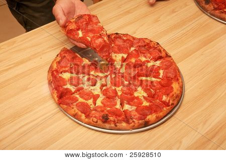 pepperoni pizza in a pizza parlor with someone taking a slice for lunch or dinner