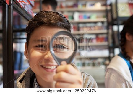 Young Cheerful Student Boy Standing In School Library And Looking At Camera Through Loupe