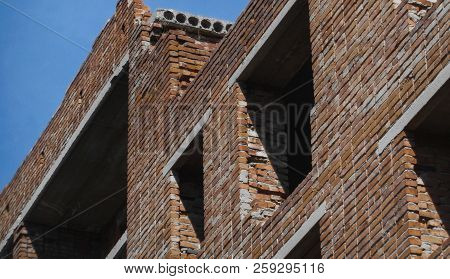 Unfinished abandoned brick building. Kazakhstan (Ust-Kamenogorsk). Incomplete abandoned residential building. Grunge architecture. Architectural background. Blue sky poster