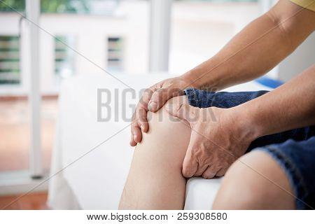 Crop Man Massaging Injured Knee
